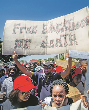 Thousands of protesters hold up signs as part of the #FeesMustFall campaign. Picture: Gallo images / Jaco Marais