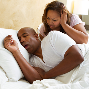 Man snoring and keeping woman awake