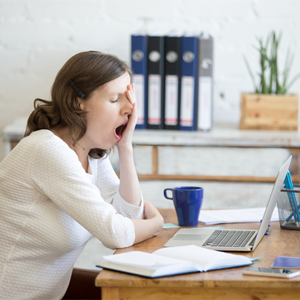Woman yawning at office desk