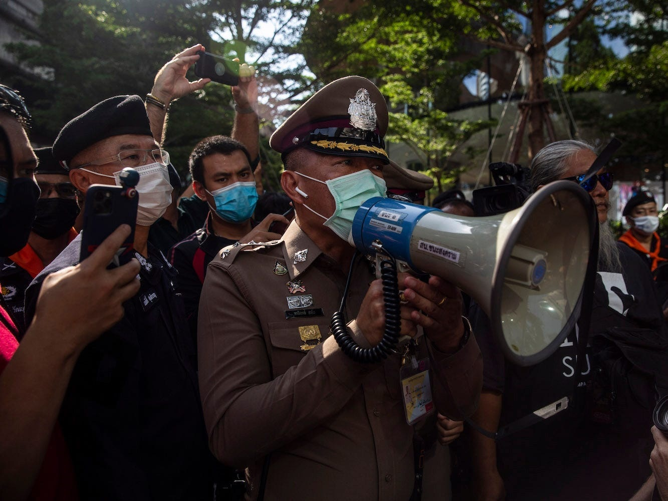 A Thai police chief speaks to pro-democracy protestors while they rally in Bangkok, Thailand.