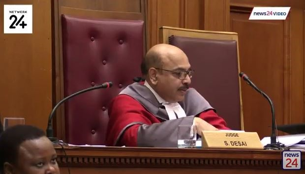 Desai asks Botha to explain the lack of blood stains in the upper part of Henri's body