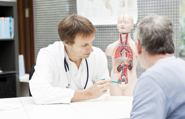 Man discussing enlarged prostate with doctor