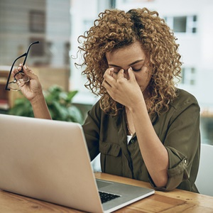 woman feeling tired at her desk