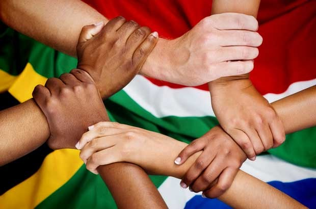 diverse hands connected with South African flag in