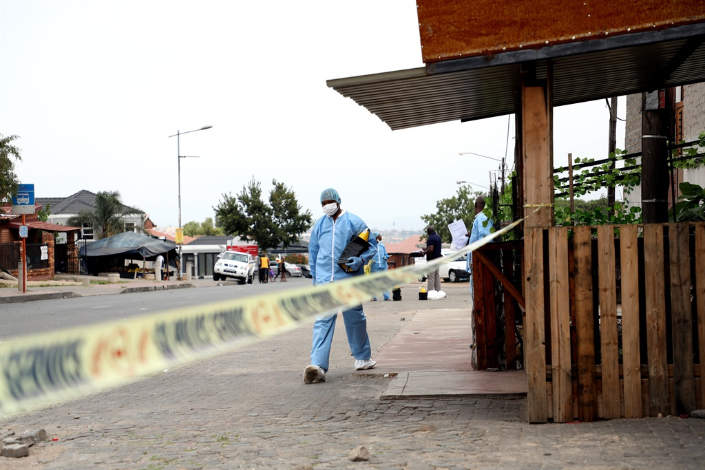 A forensic officer investigates a crime scene in Soweto.