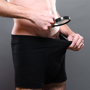 Man look in underpants with magnifying glass