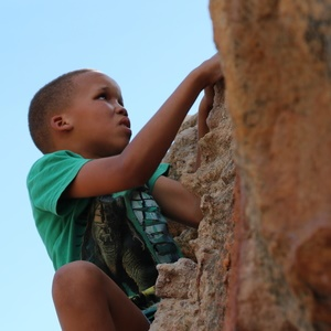 Child from RAD climbing up a rock in Cederberg. (Photo: Gabi Zietsman)