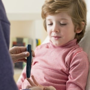 child with diabetes using glucometer