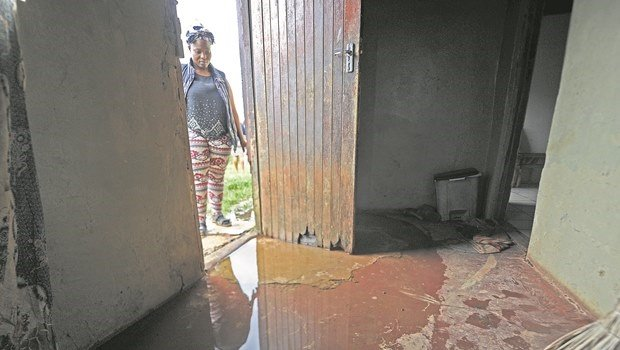 Mandisa Sithole looks at the water puddle on her home's foyer.