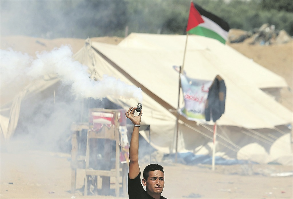 At the Israel-Gaza border in the southern Gaza Strip,a demonstrator holds a tear gas canister fired by Israeli forces during a protest by Palestinians demanding the right to return to their homeland Picture: Reuters