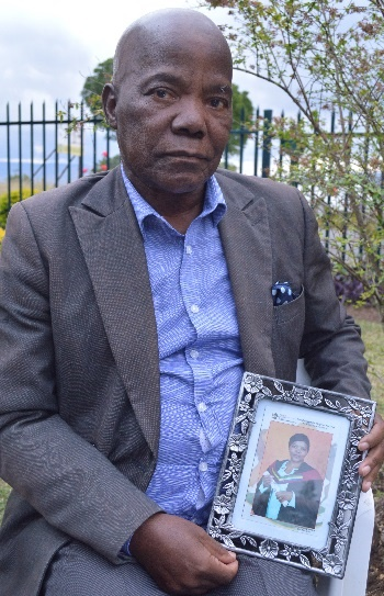 Lot Ntuli (72), the father of slain Edendale nurse Ntombizodwa Charlotte Dlamini (40) holds up a photo of his daughter at her graduation outside the house where his daughter was shot and killed.