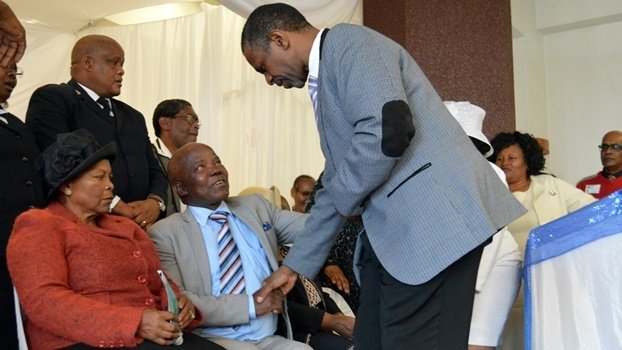 KZN Health MEC Sibongiseni Dhlomo (standing) shakes hands with Lot Ntuli and his wife Maud (left), the parents of Ntombizodwa Charlotte Dlamini. Dlamini was shot dead by her husband on Mother's Day.