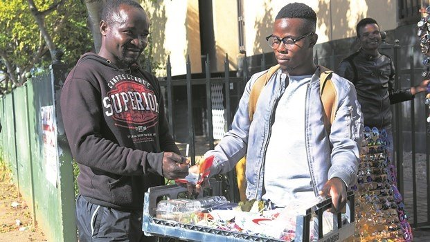 Simone Lyton buys a loose cigarette from Tony Liwonde,a street vendor, on Church Street. A proposed regulation could ban the sale of loose cigarettes.