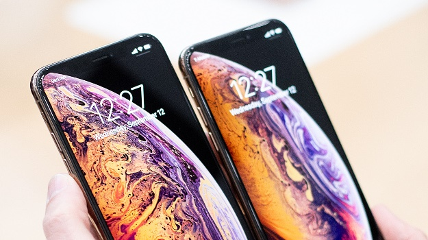 A person holds an Apple iPhone XS Max, left and iP