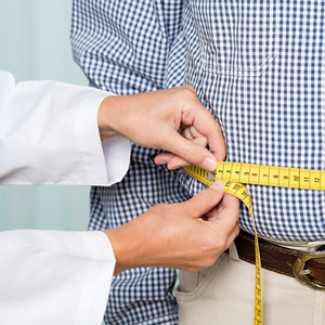 doctor measuring man's belly