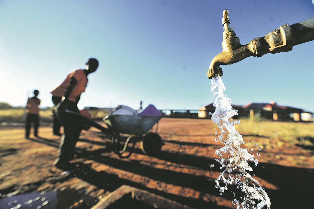 Community members fill water buckets from a communal tap in a village outside Senwabarwana in Limpopo. Picture: Leon Sadiki