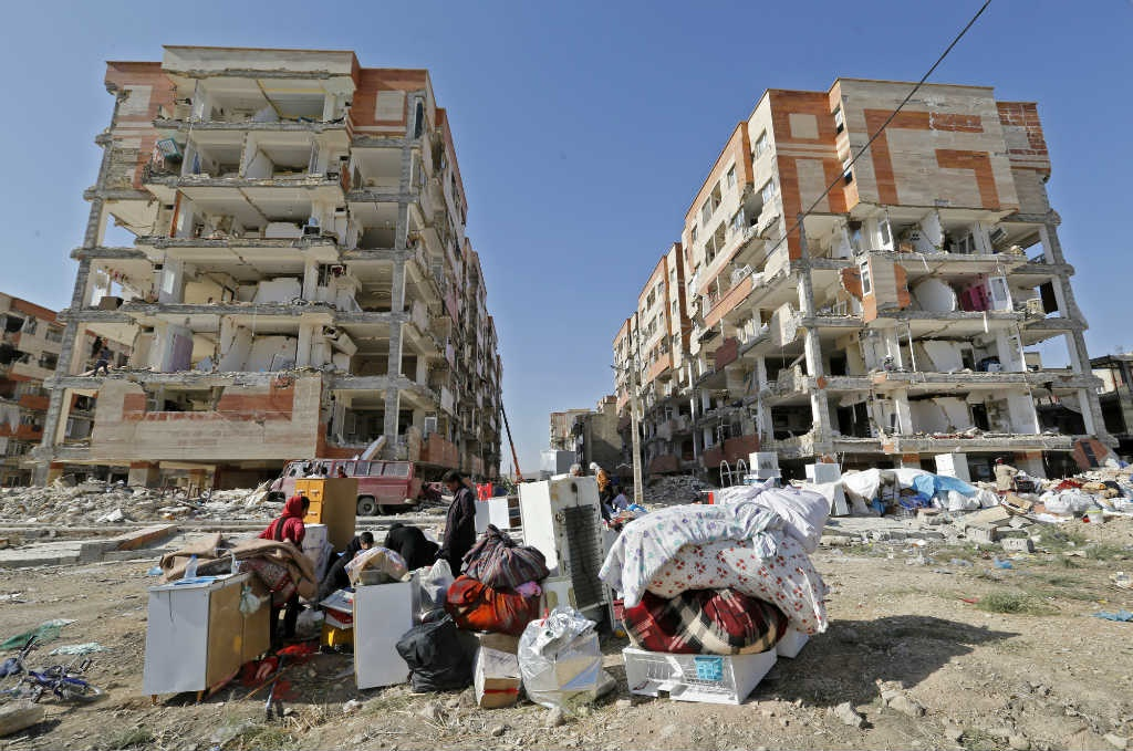 Iranians sit outside damaged homes after salvaging furniture and household appliances in the town of Sarpol-e Zahab in the western Kermanshah province of Iran. (November 15, 2017) (Atta Kenare/AFP)