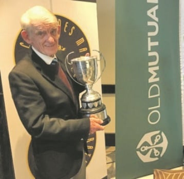 Alf Burgess   (79) collects his trophy for being the oldest finisher of Sunday's Comrades Marathon at a prize-giving function in Durban on Monday.
