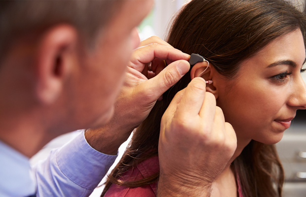 Doctor fitting hearing aid