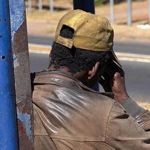 A homeless man sits on the floor at a bus stop in the Magnolia Dell park, in Muckleneuk, Pretoria. The bodies of two homeless men were discovered in this park on June 8 and 9.