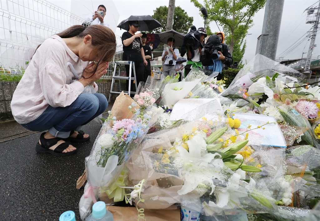 A resident praying for victims of a fire which hit the Kyoto Animation studio building the day before, killing 33 people, in Kyoto. (Jiji Press, AFP)