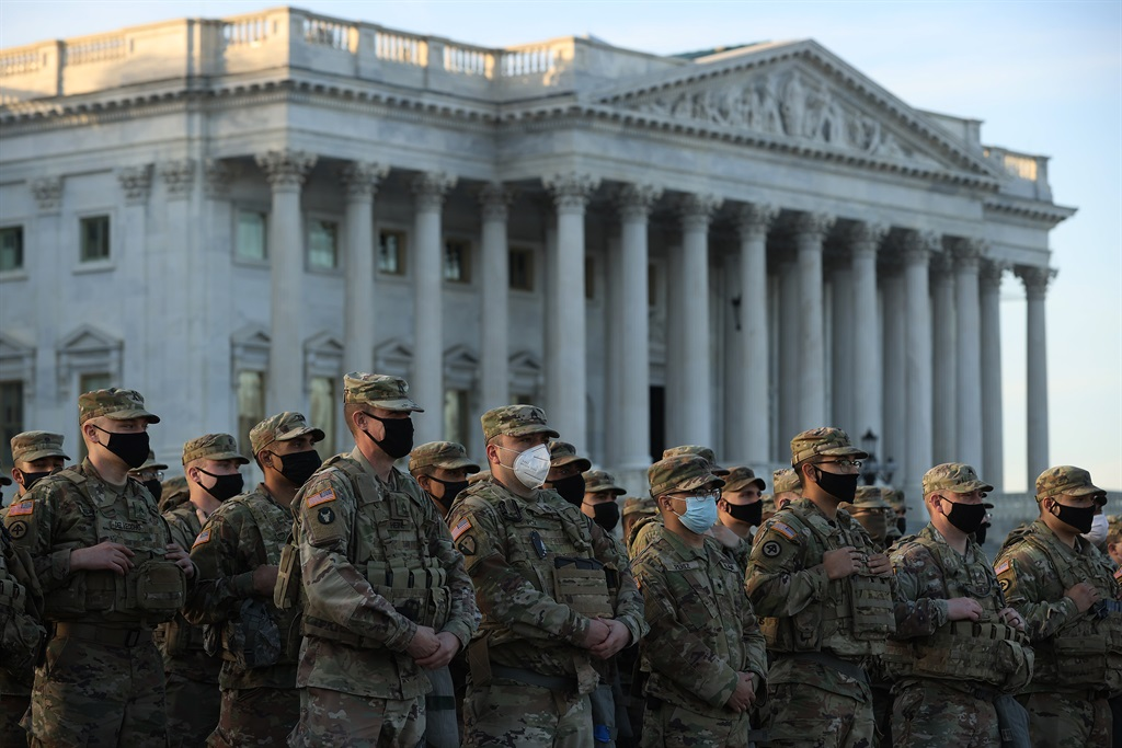 National Guard troops pose for photographers on the East Front of the U.S. Capitol the day after the House of Representatives voted to impeach President Donald Trump for the second time January 14, 2021 in Washington, DC.  (Photo by Chip Somodevilla/Getty Images)