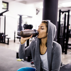 Woman drinking protein shake in gym