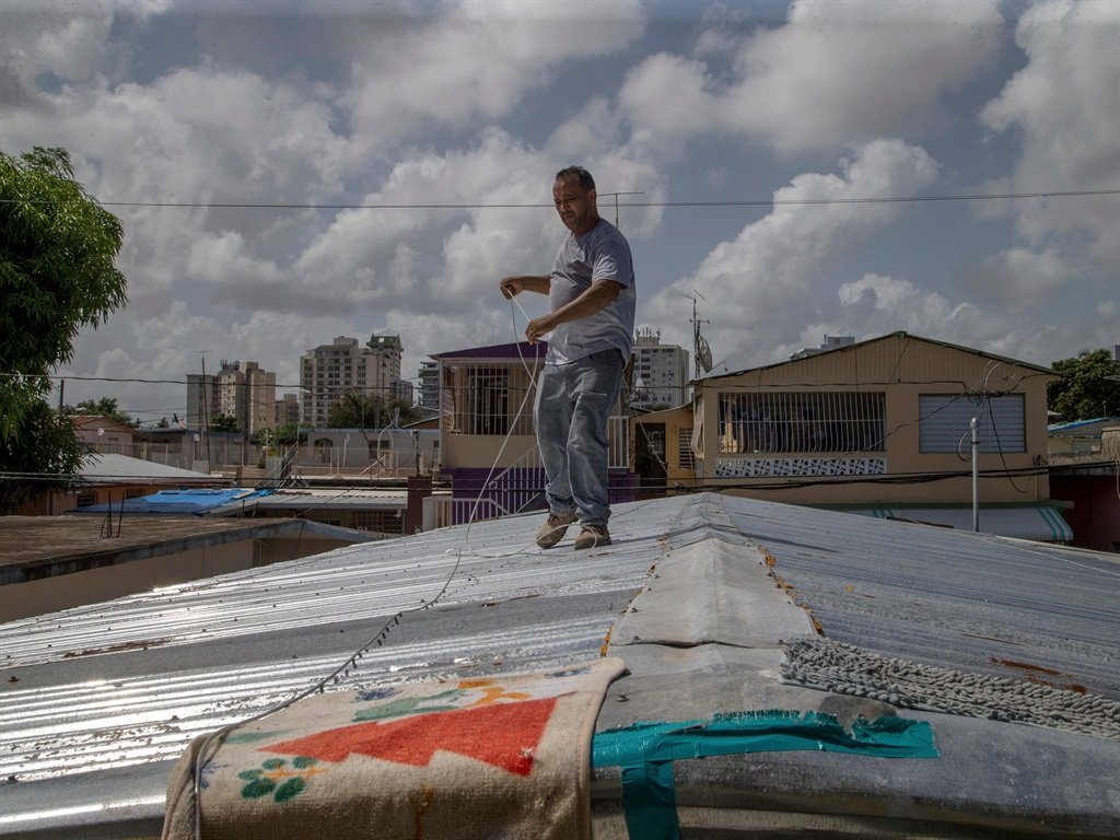 Jorge Ortiz works to tie down his roof as he prepares for the arrival of Hurricane Dorian in San Juan, Puerto Rico, August 27, 2019.