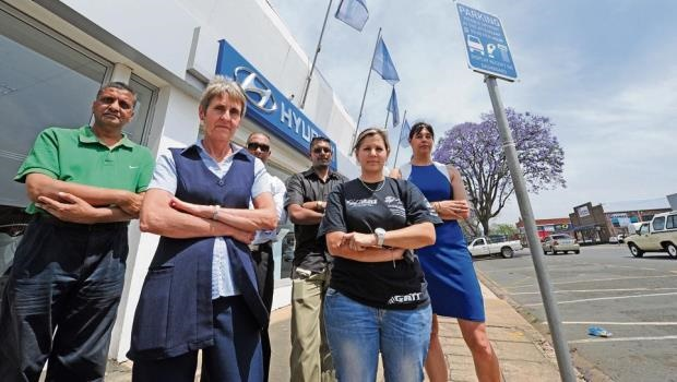 Mohamed Sheriff of FZ Auto, Debby de Koning of Oakleigh Funeral Home, Kevin Naicker of Hyundai, Pops Reddy of AC Crampton, Anel Vlok of Extreme Machines and Bridget Jones of Pronel show their disapproval outside their Greyling Street businesses after