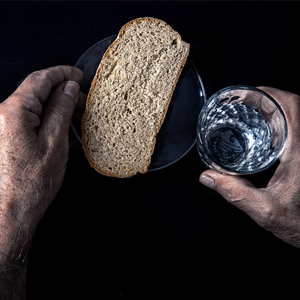 Man with bread and water on table