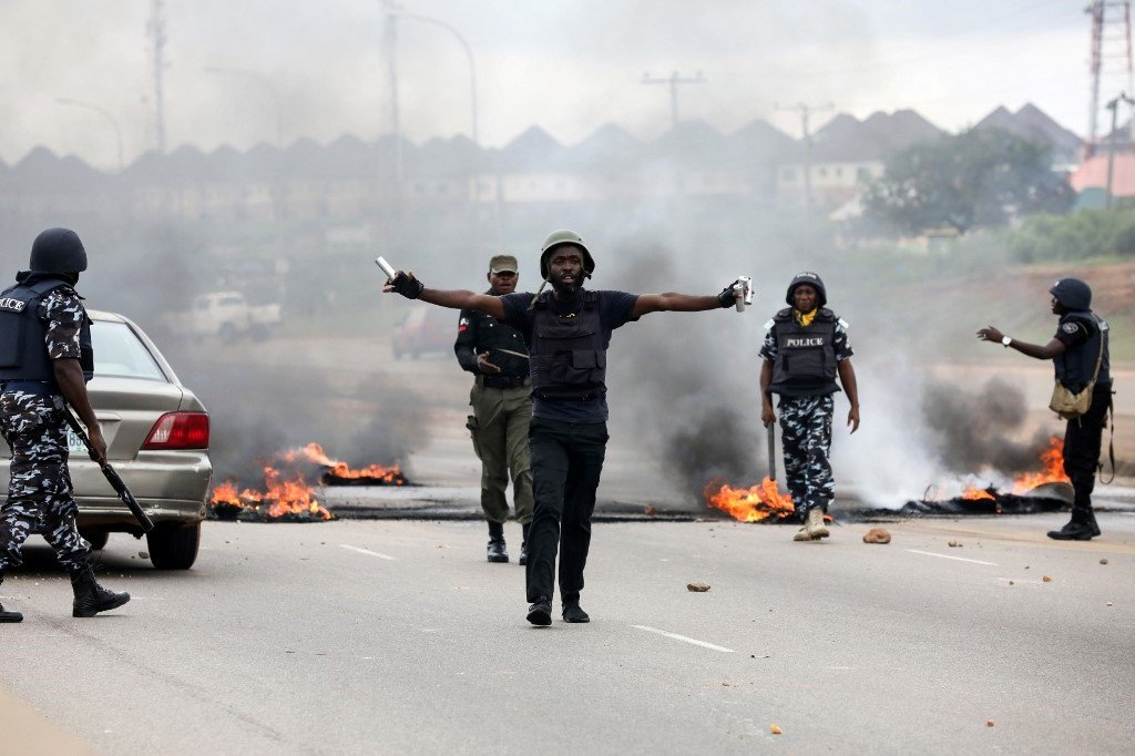 Anti-riot policemen try to calm down protesters during a demonstration and attacks against South African owned shops in Abuja, on September 4, 2019.