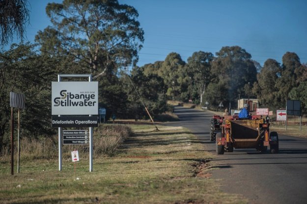 Workers drive past a sign of the Sibanye-Stillwater Driefontein gold mine near Carletonville, near Johannesburg, on May 5, 2018.