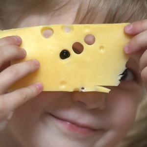 Girl holding a  piece of cheese