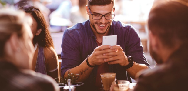 man on smartphone at restaurant