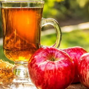 Cup of hot tea in the garden. Red apples and tea.