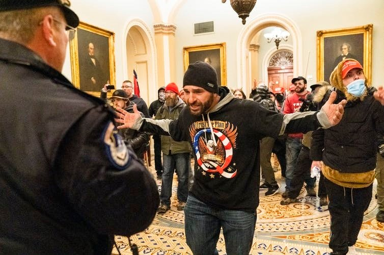 A supporter of President Donald Trump, seen wearing a QAnon shirt, is confronted by Capitol Police officers outside the Senate Chamber during the invasion of the U.S. Capitol. (AP Photo/Manuel Balce Ceneta)