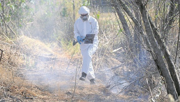 Rupert Sebire, a geologist, collects soil samples surrounding smouldering waste buried next to a train line in Merrivale on Wednesday. Janis Holmes, a Howick councillor, is also pictured.
