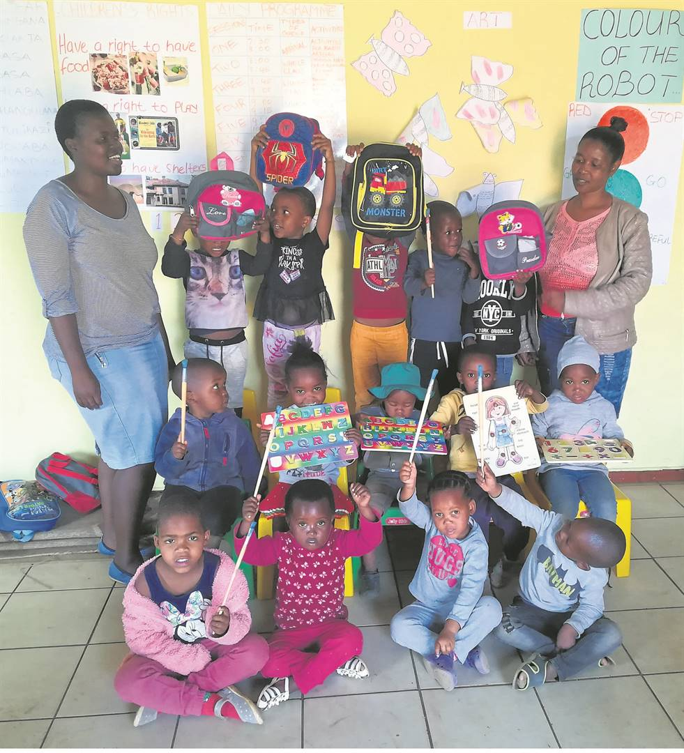 photo: suppliedCelebrating with the children at the Umvoti Aids Centre is (back, from left) Nondumiso Zuma and Bangi Luswazi.
