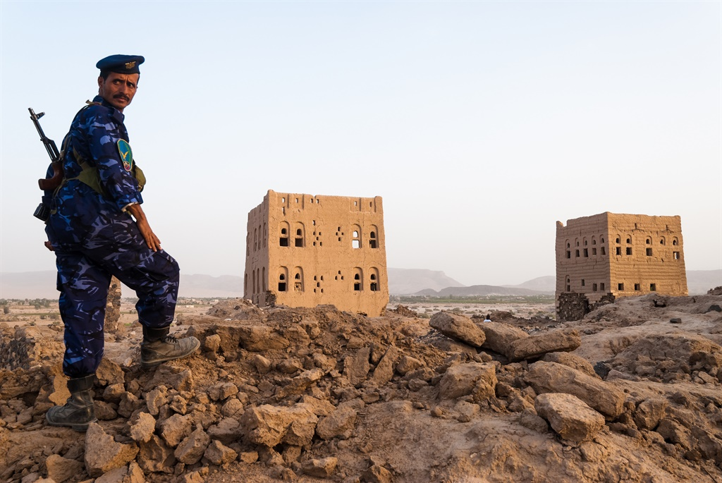 A heavily armed policeman guards an archaeological