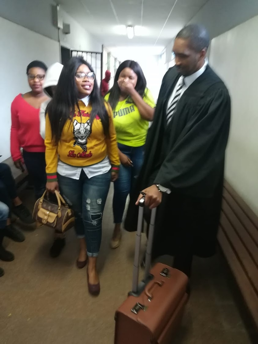 Sibongile Mani (in the yellow jersey) walks out of the East London regional court. Picture: Malibongwe Dayimani/DispatchLIVE