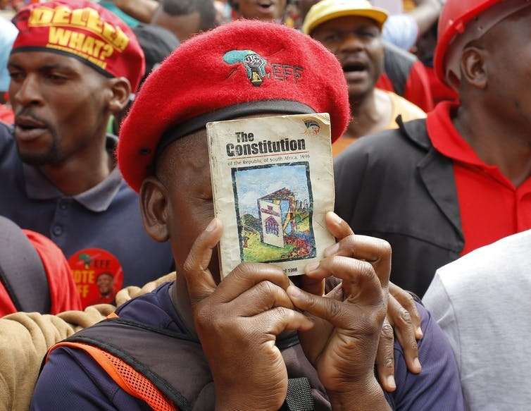 A member of South Africa's Economic Freedom Fighters party with a copy of the Constitution. Picture: Kim Ludbrook/EPA