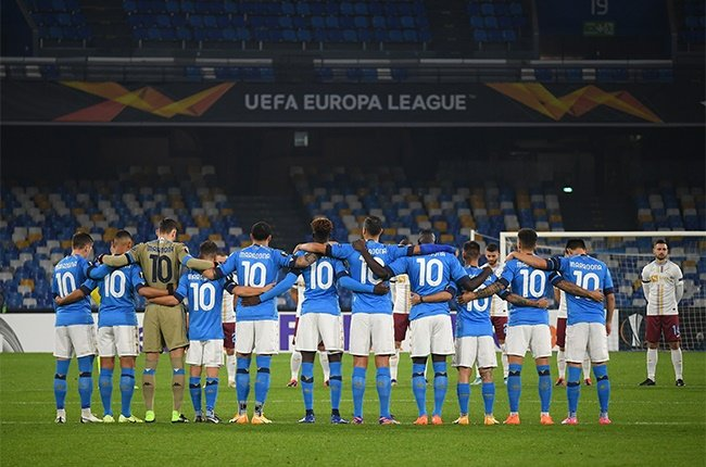 Players and Officials observe a minute of silence wearing number 10 on their shirts prior to kick off in memory of Diego Maradona while wearing a black armband on their sleeve of their shirts in memory of Diego Maradona during the UEFA Europa League Group F stage match between SSC Napoli and HNK Rijeka at Stadio San Paolo on November 26, 2020 in Naples, Italy. Sporting stadiums around Italy remain under strict restrictions due to the Coronavirus Pandemic as Government social distancing laws prohibit fans inside venues resulting in games being played behind closed doors.