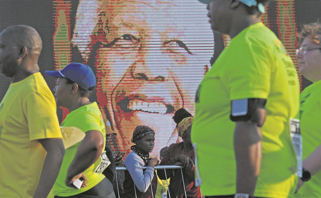 Runners pass through the finish line under the watch full eye of Mandela at the finish of the Mandela Day Marathon at the capture site outside Howick yesterday. PHOTO: Ian Carbutt