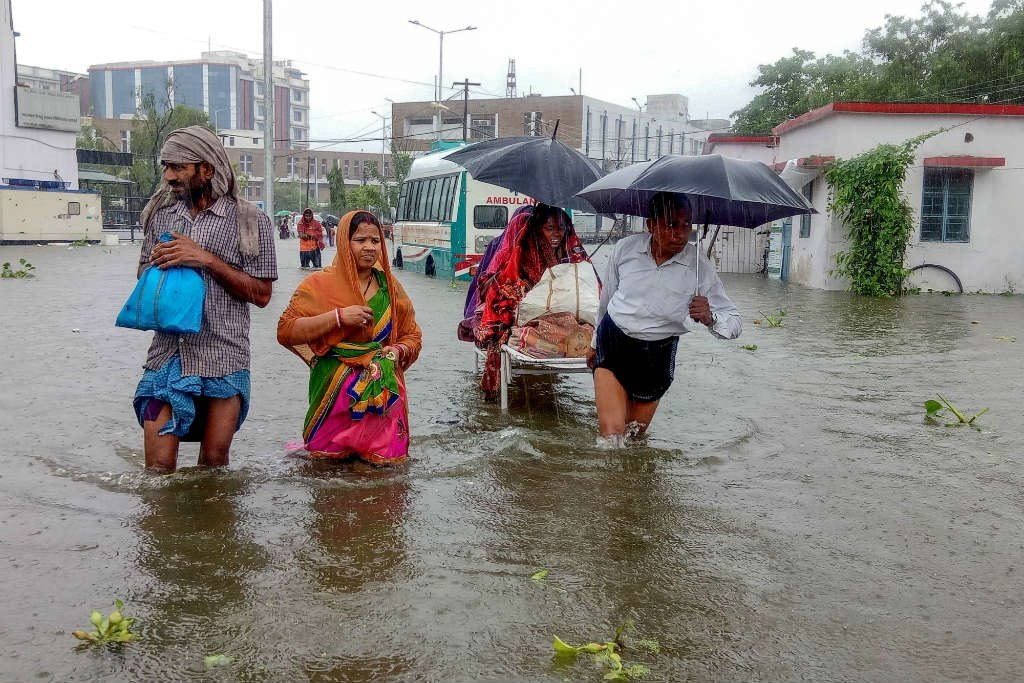 Patients wade through floodwaters on their way to hospital during heavy monsoon rain in Patna. (September 28, 2019) (Sachin Kumar/AFP)