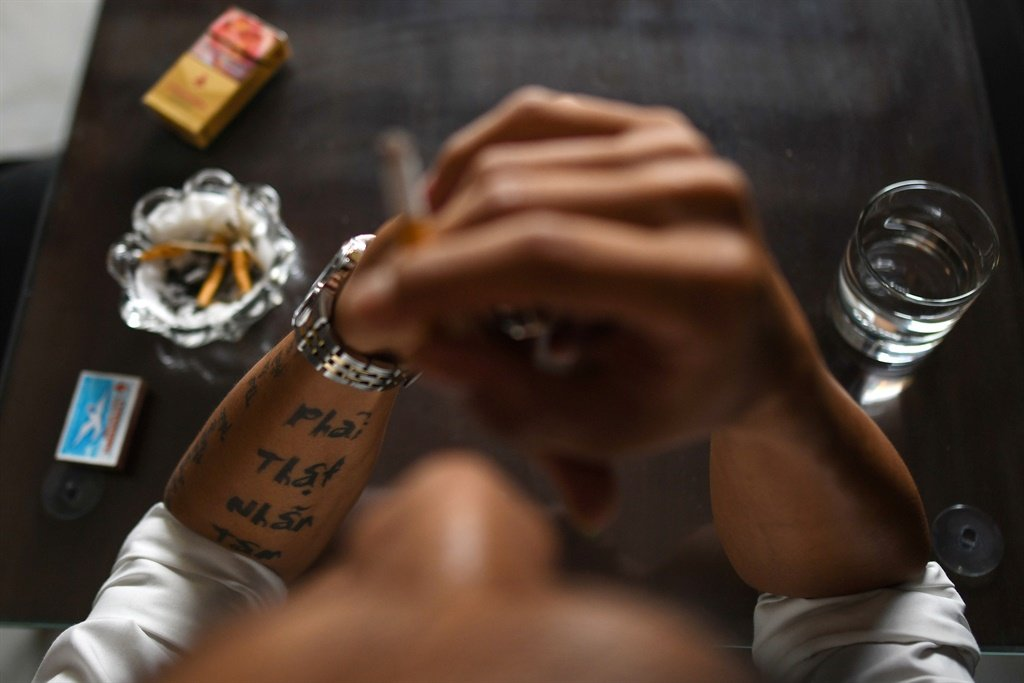"""A tattoo that reads, """"Be tough"""" on the forearm of Cuong Nguyen, a Vietnamese cannabis convict deported from Britain, while he smokes a cigarette at a cafe in Haiphong. (AFP)"""