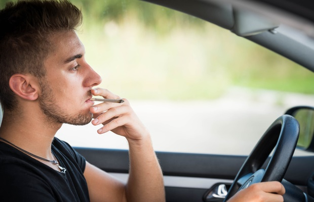 man smoking a joint while driving