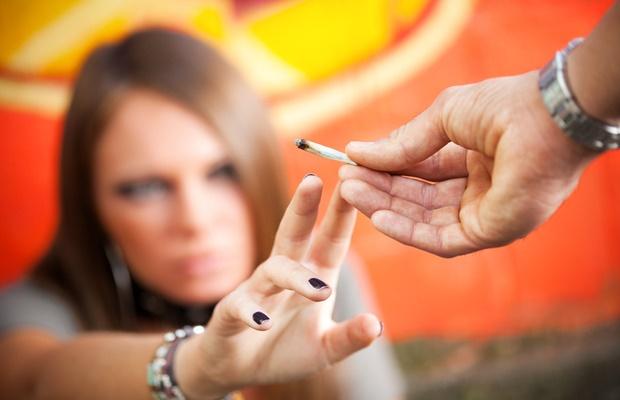 Teenager taking marijuana from man's hand