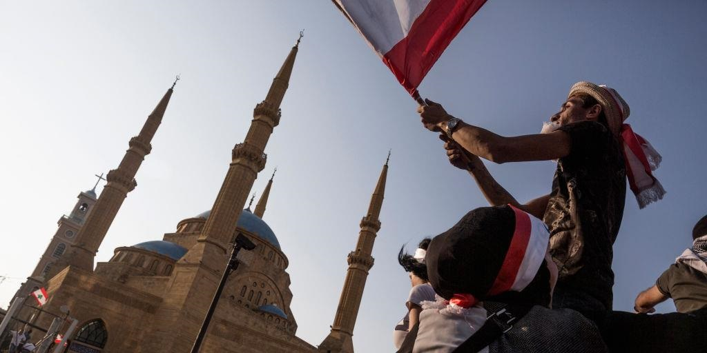 A protester waves a Lebanese flag at an anti-government demonstration on October 20, 2019 in Beirut, Lebanon.