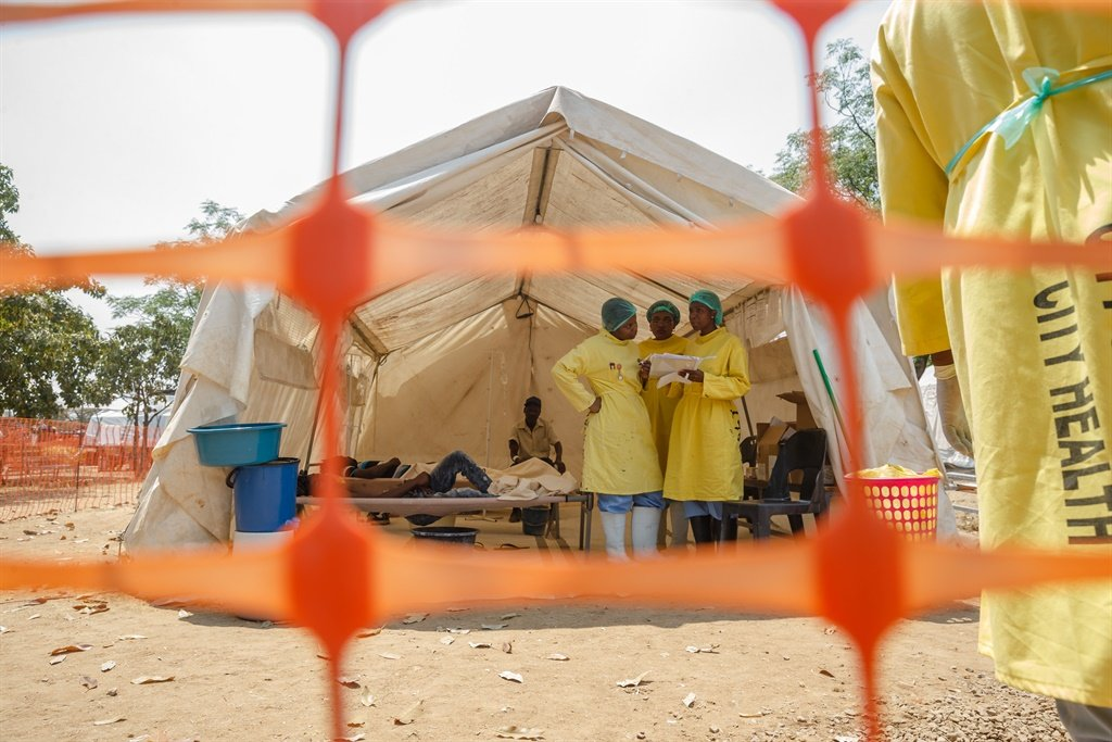 Medical staff give treatment to people suffering from cholera at a medical camp set up outside the Glen View polyclinic in Harare. (AFP)