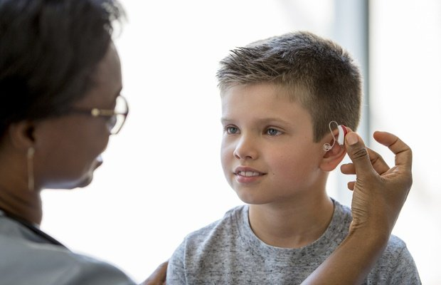Boy getting fitted with hearing aid